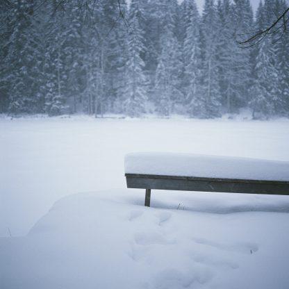 Valokuva lumeen hautautuneesta penkistä järven rannalla. Riitta Supperin valokuvavedos.