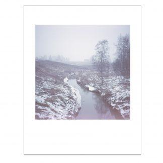 Joki kulkee pallon laitaa sumuisena talvena