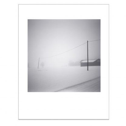 Talvinen sumumaisema jossa sähköjohto kahden tolpan välissä.