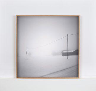 Riitta Supperin valokuvavedos Kaksi tolppaa. Sähkötolpat sumuisessa talvimaisemassa.