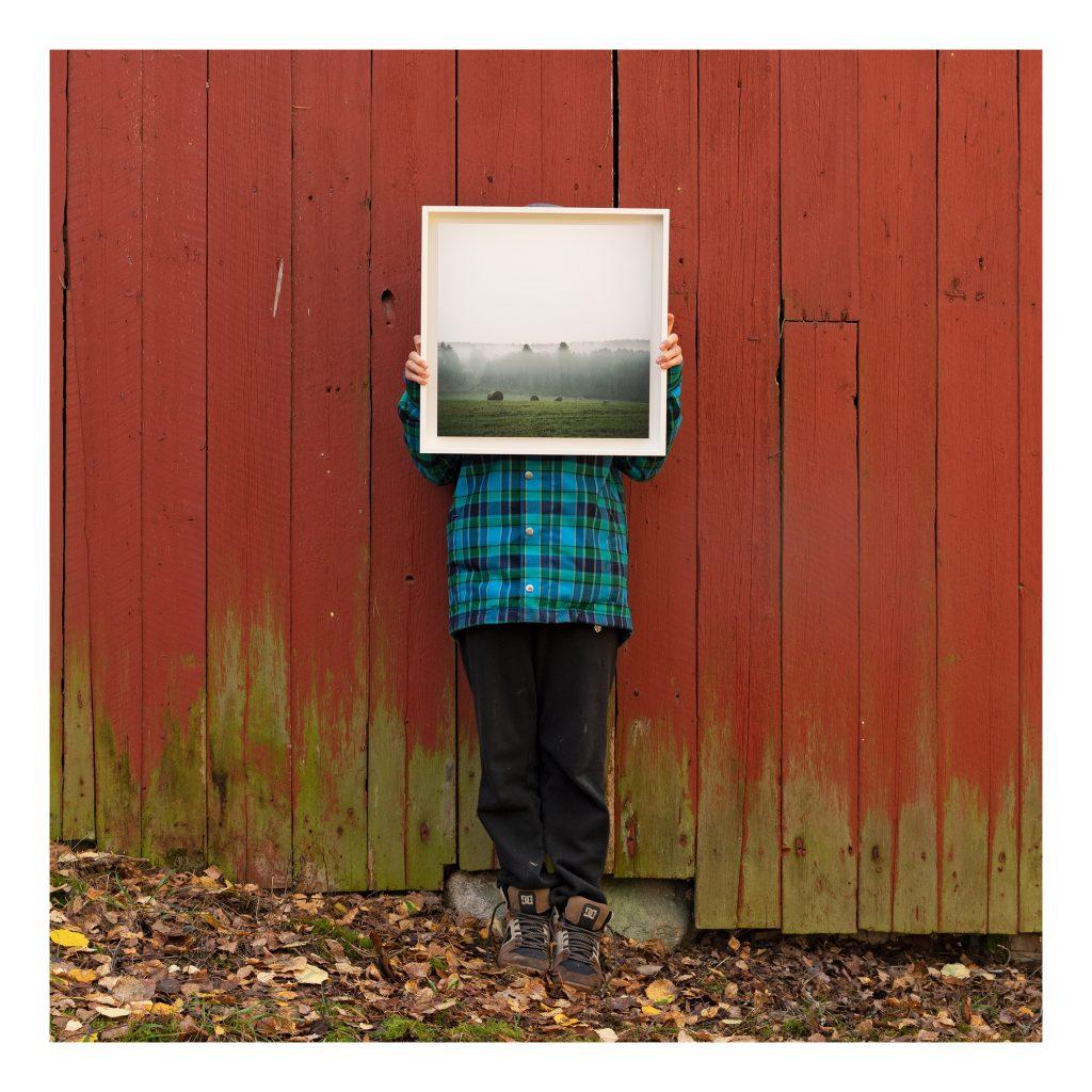 poika kannattelee kehystettyä valokuvateosta käsissään.