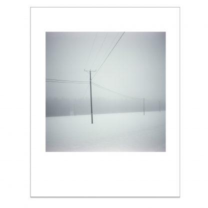 Sähköjohdot ja tolpat talvisessa maisemassa
